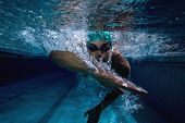 foto of swimming  - Fit swimmer training by himself in the swimming pool at the leisure centre - JPG