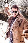 pic of snowball-fight  - a young man wearing a sheepskin coat playing with a snowball - JPG