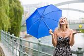 foto of rainy weather  - blond woman with umbrella enjoying the rainy weather - JPG