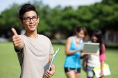 stock photo of lawn grass  - Happy College students smile to you on campus lawn asian - JPG