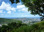 stock photo of waikiki  - Diamondhead and the city of Honolulu on Oahu bordered by trees on a nice day. UH Manoa Waikiki Kahala and the H-1 Visible seen from Round Top Dr. lookout point.