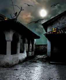 stock photo of moonlight  - Halloween pumpkins in the yard of an old house at night in the bright moonlight - JPG