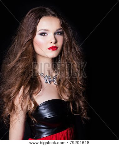 portrait of a beautiful sexy elegant girl in evening dress with a large necklace with bright festive