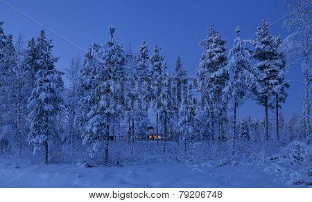 Winter landscape. Farm buildings after sunset.
