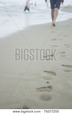 Legs Of Man And Footprints On Sand Of Beach