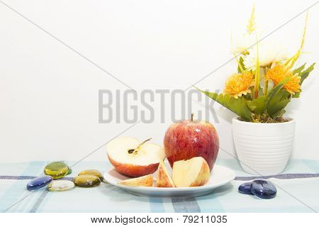 Pieces Of Apples On White Plate With Flowerpot