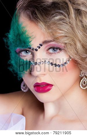 The beautiful young woman in a green mysterious venetian mask a new year carnival masquerade