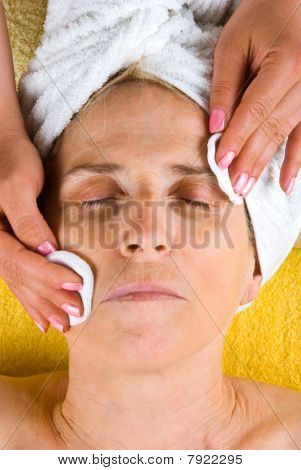 Senior Woman Cleansing Face At Spa