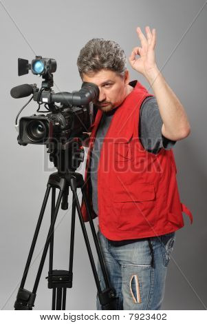 Cameraman in red vest, shows gesture