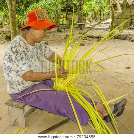 SAN MIGUEL DEL BALA, BOLIVIA, MAY 11, 2014: Local woman shows how to make a fan from palm leaves