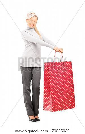 Full length portrait of a woman holding a big shopping bag isolated on white background