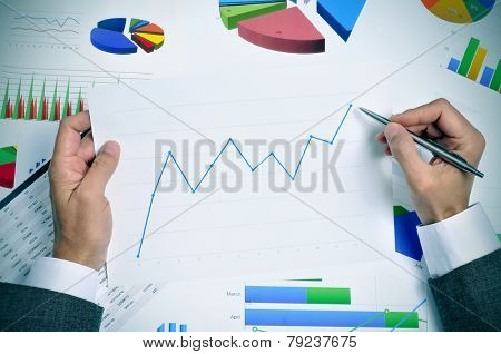 businessman in his office desk full of graphs and charts observing a chart with an upward trend