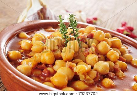 closeup of an earthenware bowl with potaje de garbanzos con jamon, a spanish chickpeas stew with ham