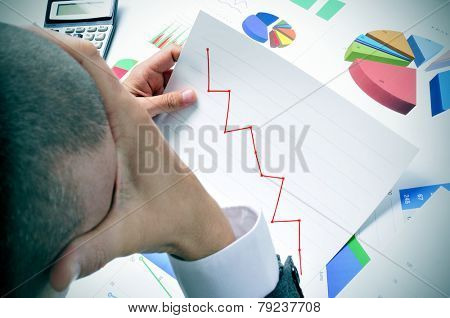 businessman in his office desk full of graphs and charts observing worried a chart with a downward trend