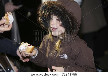 Little girl enjoying sufganiyot