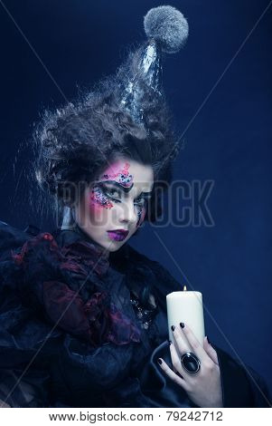 Young woman with creative make up holding candle. Halloween theme.