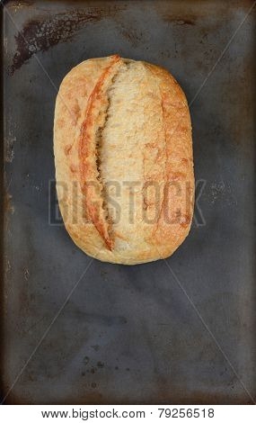 High angle shot of a fresh baked loaf of bread on a baking sheet. Vertical format with copy space.
