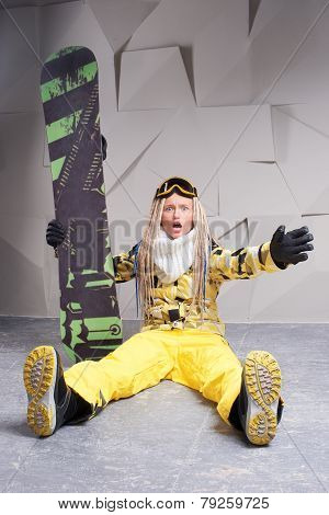 Surprised woman sitting on floor with snowboard