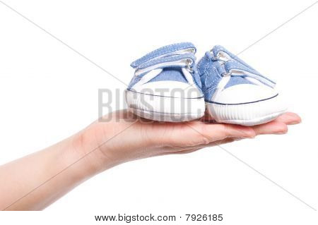 Female Hand Holds Small Baby Shoes, Isolated