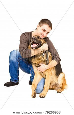 Happy young man embracing a German shepherd
