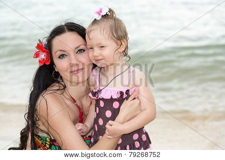 Happy Mom And Child Girl Hugging On Tropical Beach. Sea, Water And Family Background