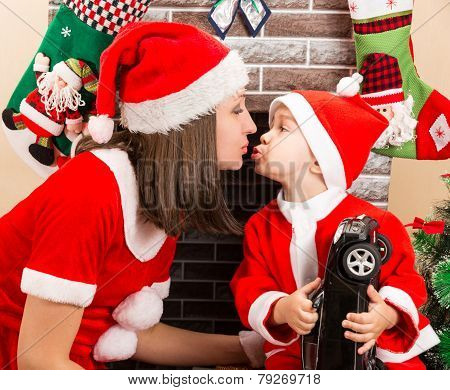 Happy Mother And Child Boy Cuddling  Dressed Costume Santa Claus By Fireplace. Christmas And New Yea