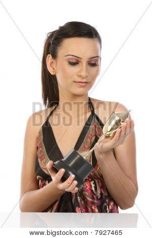 beautiful teenage girl feeling happy by seeing her gold trophy
