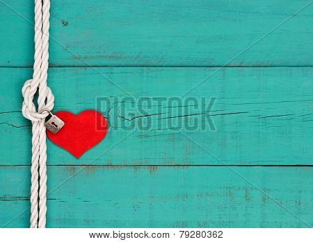 Red heart and lock hanging from knot on white rope border against blue wooden background