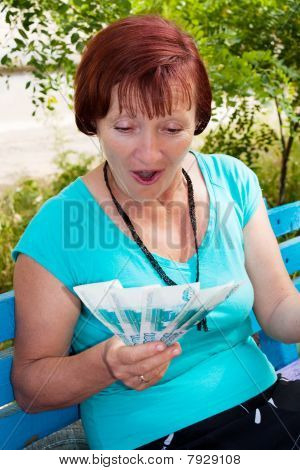 The Elderly Woman Sits In Park In Hands Of Money