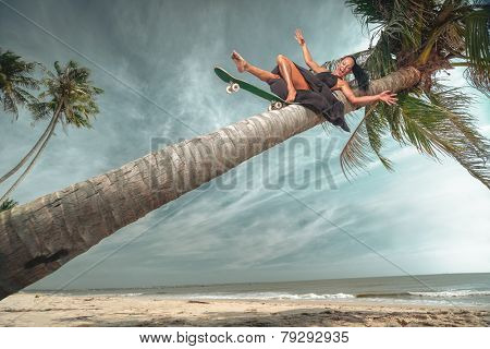 Beautiful and fashion young woman riding down coconut palm with a skateboard on beach