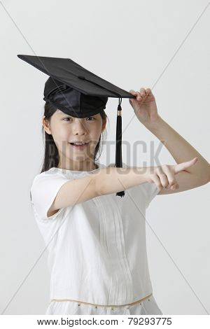girl with the mortar board pointing