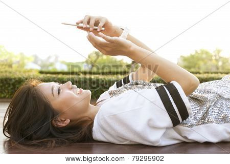 Young Beautiful Woman Lying On Home Terrace And Playing Smart Phone In Hand Use For People And Moder