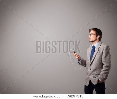 handsome young man singing and listening to music with copy space