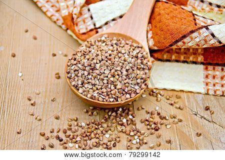 Buckwheat in spoon and napkin on board