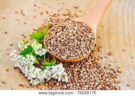 Buckwheat in spoon on board with flower