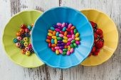 image of beads  - Multi colored beads in colourful dishes on white wooden table - JPG