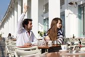 stock photo of waiter  - Portrait of a young man sitting at outdoor cafe with raised arm asking for waiter - JPG