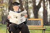 stock photo of professor  - Mature college professor reading the news in park seated on a bench - JPG