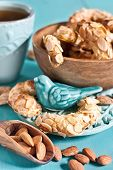 pic of crescent-shaped  - Homemade almond crescent cookies on teal background - JPG