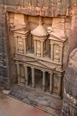 stock photo of treasury  - The Treasury in the Ancient city of Petra carved out of the rock Jordan as seen from the cliff - JPG