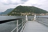image of dock a lake  - The lake and the city of Como ferry dock in the background the funicular Como to Brunate where you can enjoy a splendid panorama of Como and its lake view Villa Olmo Como Lombardy Italy - JPG