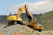 pic of track-hoe  - Large tracked excavator loading a articulated dump of rock - JPG