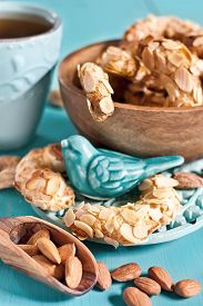 foto of crescent-shaped  - Homemade almond crescent cookies on teal background - JPG