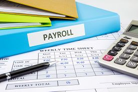 stock photo of summary  - PAYROLL word on blue binder place on weekly time sheet and payroll summary report human resources concept - JPG