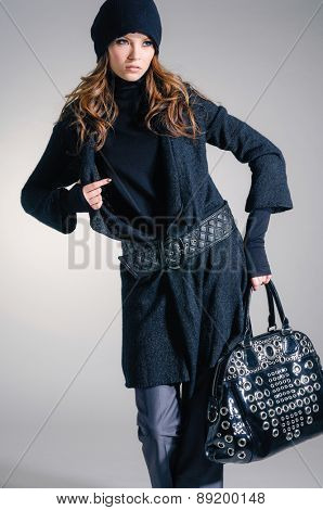 Portrait of fashion model in autumn/winter clothes holding handbag posing