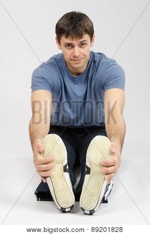 The Young Man Stretches Muscles Of Legs