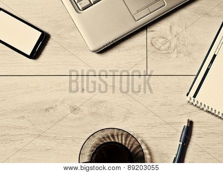 Office table with laptop, phone, notebook and coffee cup