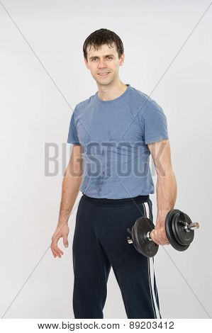 Portrait Of An Athlete With Dumbbells In The Hands