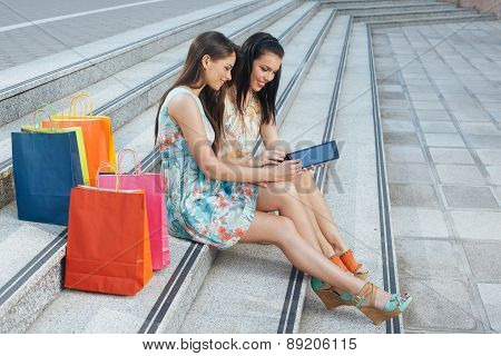 Two Young Women Buying Online Through A Digital Tablet