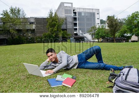 male college student lying on use laptop on a campus